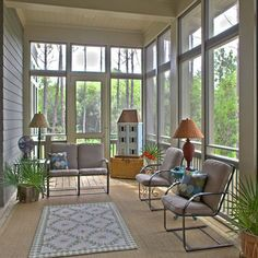 This is a very beautiful screened in porch on the front of a house.