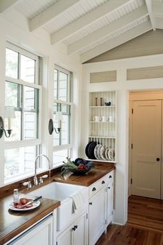Country Kitchen with Norwell newport shaded wall sconce, Wood counters, dishwasher, European Cabinets, double-hung window