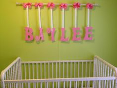 Wall hanging. Letters were cut out of wood, sanded and painted.  They were hung with ribbon from a wooden curtain rod.