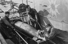 Crew of U-124 prepping and loading a torpedo