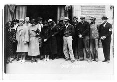 In this photograph, residents of Liberal, Seward County, have donned gas masks to protect their lungs from blowing dust. The photograph was taken in front of the Red Cross building in Liberal, Kansas.    Date: 1935