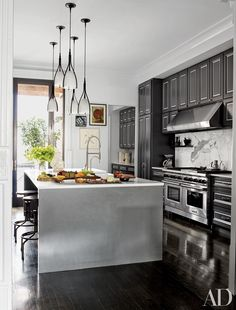 For Neil Patrick Harris and David Burtka's New York City townhouse, interior designer Trace Lehnhoff handled the renovation in collaboration with the architecture firm Povero & Company. Pendant lights are suspended above the Caesarstone-top island in the kitchen, which is equipped with a Wolf range and hood.