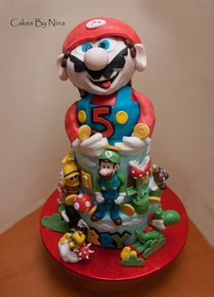 A sculpted Mario cake. Including characters and icons from the game.     Its Mario and Company  Cake by cakesbynina