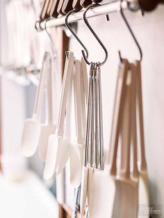 Metal towel bars can serve a new purpose in the kitchen when you install them inside a cabinet or pantry door, or mounted to the wall. Use the bar to store lids in your pots and pans cabinet. You can also hang cooking and baking utensils from S-hooks.