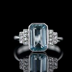 *this with princess cut and my choice of rocks would be great* Aquamarine and diamond ring, c. 1920s-1930s. This ring features a soft blue 2.26 carat bezel set emerald cut aquamarine in a clean Art Deco style mount of 18 karat white gold. Flanked in an architectural step design so popular in the Deco period we have scintillating single cut diamonds
