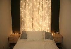 white string lights behind sheer curtain, bedroom