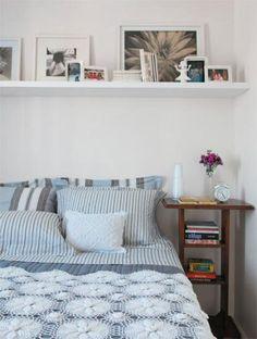 Para exibir várias fotografias, a prateleira fixada sobre a cama de casal cumpre bem a função. Todos os quadros (Fast Frame) ficam apoiados na parede e podem ser trocados facilmente. Os porta-retratos são da Tok&Stok e o enxoval da Trousseau. Projeto da decoradora Maristela Gorayeb.
