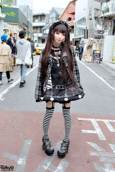 TokyoFashion.com: Ringo's look includes a jacket, net top and puffy skirt plaid skirt all from h.NAOTO, striped garter socks, and chunky spiked heels from Yosuke USA. Accessories include a labret piercing, multiple ear piercings, a plaid headpiece, a skeleton hands necklace, a studded leather choker, a Vivienne Westwood armor ring, an eyeball ring, other silver rings, and Algonquins backpack.