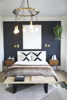 Dark blue accent wall, graphic throw pillows and a chandelier in the bedroom