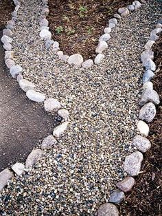 Inexpensive gravel walkway - line with landscape fabric, border with stones and fill with pea gravel.