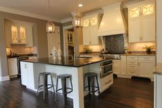 Microwave on side of island, lights in upper kitchen cabinets, vent hood design, lights -  all so nice