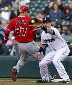Game #46 5/24/12: Seattle Mariners first baseman Mike Carp, right, catches the ball on a pick-off attempt on Los Angeles Angels' Mike Trout in the first inning in a baseball game Thursday, May 24, 2012, in Seattle. Trout was safe on the play. (AP Photo/Elaine Thompson)