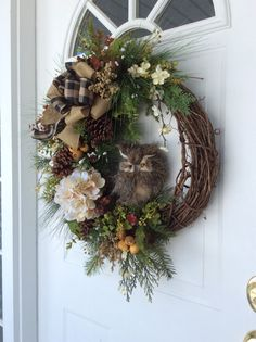 Winter Wreath-Owl Wreath-Wreath for Front Door-Winter Owl Wreath-Reginas Garden Owl Wreath-Rustic Wreath-Evergreen Wreath  A beautiful mix of evergreen boughs creates a lush woodland backdrop for a realistic, great horned owl, sitting on his perch. Seeded eucalyptus, woodland ferns, cedar, heather, creamy white flower stems, hydrangea, large pine cones and eucalyptus pods add to the rustic charm of this design. This natural, woodland wreath is finished with a double bow of black and tan…