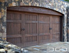 This Tuscan Style Garage Door was handcrafted in solid rustic alder wood with an oil rubbed finish and decorative iron hardware. The Tuscan garage door design complements the stone construction of the home with the rustic wooden header beam that was Custom Garage Doors, Garage Door Hardware, Carriage Garage Doors, Modern Garage Doors, Wood Garage Doors, Garage Door Colors, Garage Door Windows, Garage Door Styles, Garage Door Design