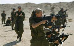 Female Israeli soldiers fire their weapons during a training session at military base in southern Israel February 12, 2007. Six Israeli women who feature in the documentary ''To See If I'm Smiling'' each wrestle with memories of their compulsory military service that they would rather erase. REUTERS/Eliana Aponte