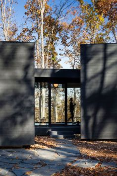 This house has a glass door beside glass windows that allow you to see through the house to the other side.