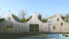 This school byStudio Weave features a scalloped roofline and double doors that slide back to connect the classrooms with theirwoodland setting.