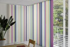 Originales cortinas verticales con lamas de distintos colores en la sala de estar.
