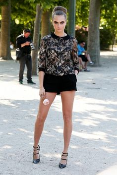 Cara Delevingne wears a lace top, black shorts, and black strappy pumps