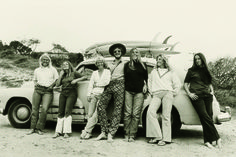"Photo of ""Nat and the girls with Judy Trim's Buick"" by iconic Australian surf photographer, John Witzig at a surfing contest in Australia in 1972. From left to right: Kim McKenzie, Micha Mueller, Phyllis O'Donell, Nat Young, Judy Trim, Carol Watts and Alison Cheyne."