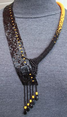 For this necklace I actually started by trying to get rid of some leftover black cubic beads.  Since black would be very dismal standing all alone I added some almost neon orange highlights.... So the necklace developed - and it came out quite pleasant I think... I like it. Hope you like it, too. ;-)    Measurements:  Neck down to the longest fringe: 52 cm (20 1/2 inch)