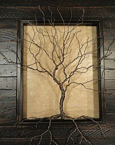 This beautifully crafted wire tree sits inside a distressed, dark brown stained, salvaged wood look photo frame. Its branches and roots reach up, out and over the frame, grabbing into nooks and crannies in the frame to hold itself in place, making this tree have a unique 3-D appearance. Tree is made from 22 gauge antique brass and hematite wire, giving it a wonderfully textural and life like look. Frame measures 13 3/4 x 11 3/4in, frame opening measures 7 x 9in.  Saw tooth hook for hanging…