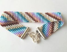Miyuki delica bead bracelet, made using a bead loom. Beadwoven pattern of bands of colour including silver, white, 2 shades of blue, pink, purple, burgundy. Measures 7 with a 2 extender.