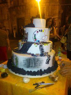L'arte è anche artigianato per il palato, in diretta dalla pasticceria del maestro Santo Musumeci & figli, all'opera in piazza Santa Maria con alcuni collaboratori su un esempio di splendida torta in pasta di sale decorata con colori alimentari.