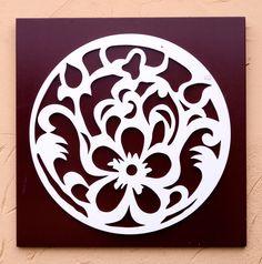 Mandala branca sobre fundo cor marrom, feita em MDF. Motivo floral.