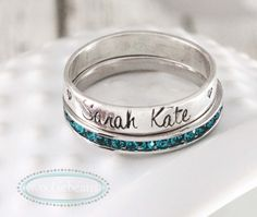 Stackable name birthstone rings in sterling silver are personalized just for you. Silver bands are hand stamped and paired with eternity birthstone rings.