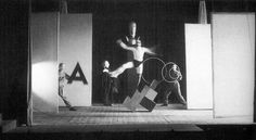 Theater students wearing Schlemmer's masques, exercising with simple accessories (equilibrism) on the Bauhaus stage.
