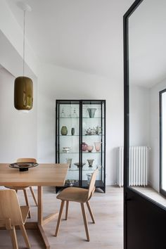 """In the dining room, the windows are matched by a two-doored Gorka Vitrine by AM.PM, """"a quite economical brand,"""" says Harden, from online retailer La Redoute (which offers free worldwide shipping on orders over $119). The oak Heldu Chairsand Kuskoa Table are both Jean Louis Iraztzoki designs from French furniture brand Alki. The hanging light is theChouchin 2 from Ilonna Vautrin's collection of mix-and-match colored glass pendants by Foscarini of Milan and NYC."""