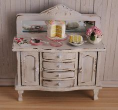 Miniature Shabby Chic Buffet With Filled With A Cake On A Pink Glass Stand, A Slice Of Cake, Roses, And A Pretty Tea Towel. $75.00, via Etsy.