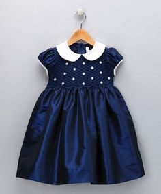 This party-perfect frock shows off a smocked bodice and charming Peter Pan collar. An attached sash adds an extra-festive touch.