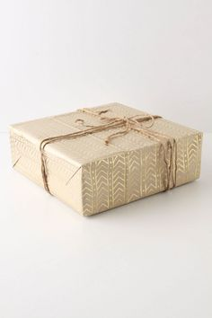 Brown kraft paper + metallic gold pattern, all tied off with natural twine = a great understated gift wrap