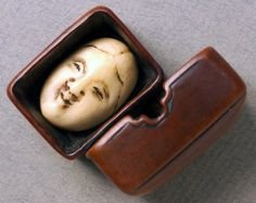 Wooden Netsuke in the form of an open box with an ivory face inside.