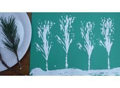 Snowy tree pictures made by dipping fir tree branches in white paint - could use different types branches from different types of tree to create different effects.