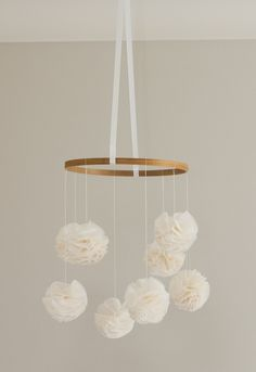 """A one of a kind baby mobile, handmade with ivory pom poms. The 9"""" in diameter hoop has eight gorgeous hand stitched poms hanging from it at various heights. Hundreds of chiffon petals make up the eight ivory poms, ensuring each pom is lovely and full. The mobile is held together by a beautiful satin ivory ribbon and each pom is suspended from the hoop on a matching thread. Each pom is approximately 3 inches in diameter.  With the soft, romantic feel of the chiffon this mobile is the perfect…"""