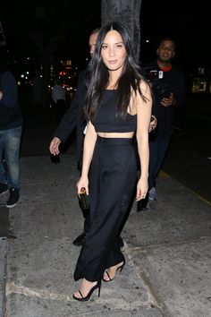 Olivia Munn (The Row trousers, Aritzia crop top) looking chic in black
