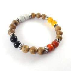 BRACELET OF THE FOUR ELEMENTS IN ACCORDANCE WITH THE INDIAN MEDICINE WHEEL  -Handmade in Italy-   Stretch Bracelet with beads from 8 mm representing the four elements in the tradition of the American Indians.   COMPOSITION  Wenge Wood White howlite-North Red coral-South Black Obsidian (Apache Tear West) Yellow agate-East   SYMBOLOGY  North is where sits the MIND whose symbol is the air; you sit or sleep North to find the necessary strategies to solving practical problems that life presents…