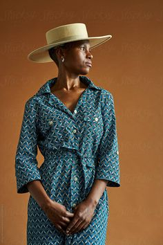 A South African woman wearing a hat and traditional Shweshwe print clothing shot against a brown background Stylist: Bielle Bellingham Photographer: Micky Wiswedal Hat: Crystal Birch Wearing A Hat, Female Portrait, African Women, Birch, Panama Hat, Wrap Dress, Stylists, Women Wear, Crystal