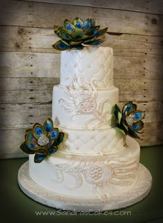 Peacock inspired wedding cake with hand painted gumpaste flowers.