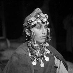 - Besancenot Jean (1902-1992)  Femme Ahel Massa non voilée. Elle porte le drapé bleu de Khount. Les boucles d'oreilles traversent l'oreille et sont maintenues par des chaînettes, talgamout. Le diadème est monté avec de longues perles de corail et de petites pièces d'argent mises de profil. Elle a le collier d'amulettes de cuir ainsi qu' un collier composé en partie d'une enfilade de clous de girofles semblables à ceux portés dans l' Atlas. - Arago