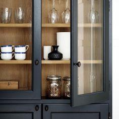 Vitrineskab i blåsort farve passer både til køkken og stue. Smalt skab, med glaslåger, hylder og bagbeklædning i fineret eg i overskab. Underskab har en hylde.