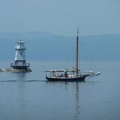 Lake Champlain, Burlington, Vt. as sailboat passes lighthouse.