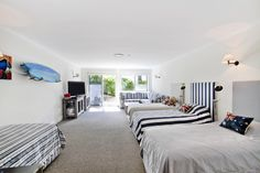 Super spacious bunk room complete with comfortable lounge and television zone. Beach House, Lounge, Bed, Room, Furniture, Home Decor, Beach Homes, Airport Lounge, Bedroom