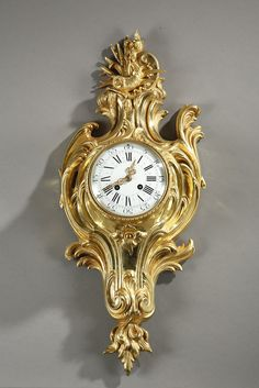 Gilt bronze wall cartel clock in Louis XV style, decorated with leaves winding around the movement with an enameled dial with Roman and Arabic numerals. The upper part is decorated...