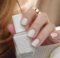 Manicura color blanco con línea casi invisible color dorado estilo francés.