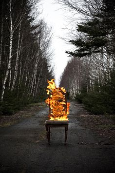 This makes perfect sense. plunk a chair in the middle of a country road, and catch it on fire. It still looks cool though.