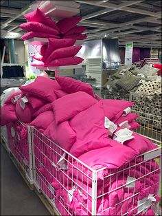 Pillows overflow from this IKEA Ceiling Rack for Pillows into open wire bulk bins below and beyond. There is so much color that you might initially overlook the ceiling fixture. Bed N Bath, Ikea Bed, Textiles, Cushions, Pillows, Ceiling Fixtures, Bean Bag Chair, Ikea Ideas, Display